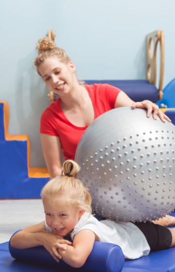 Physiotherapist massaging the girl's back by big silver ball